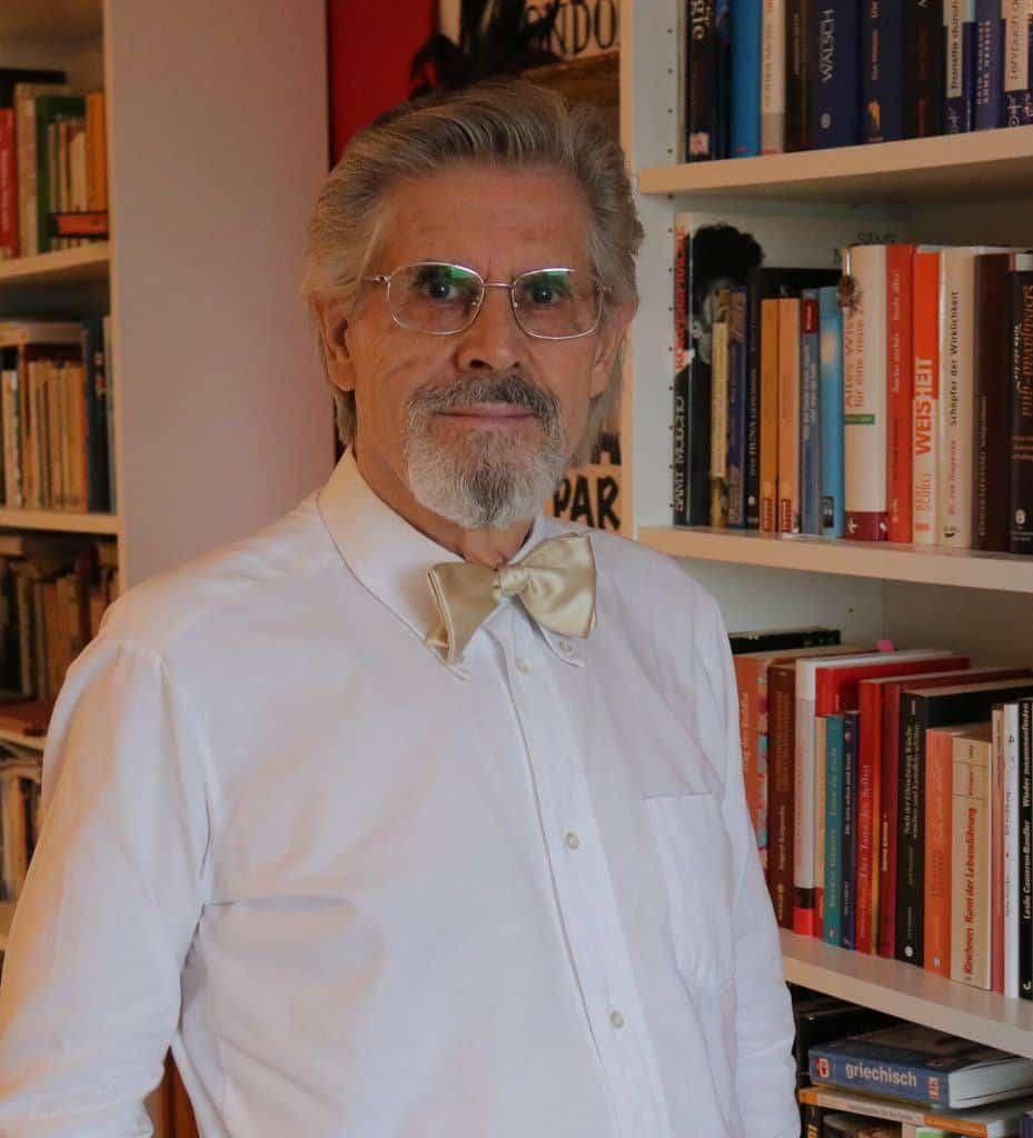 Mentaltrainer und Astrologe Manfred Peter Lederer vor einem Bücherregal